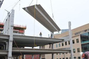A precast parking structure panel is being hoisted in by a crane with the assistance of several workers.