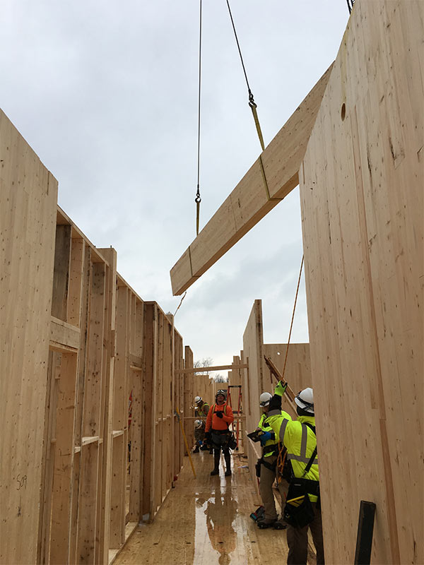 Cranes lift wood into place at Ft. Drum.