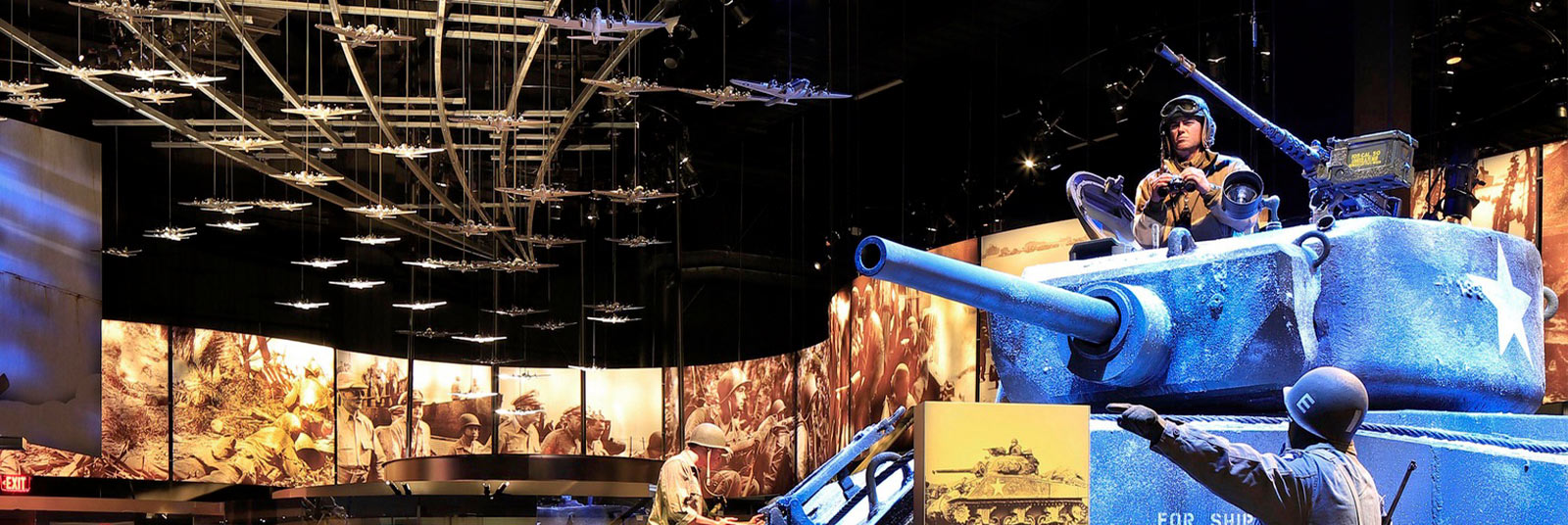 Exhibit space inside the National Museum of the United States Army featuring a tank, lit photo wall and suspended planes on the ceiling.