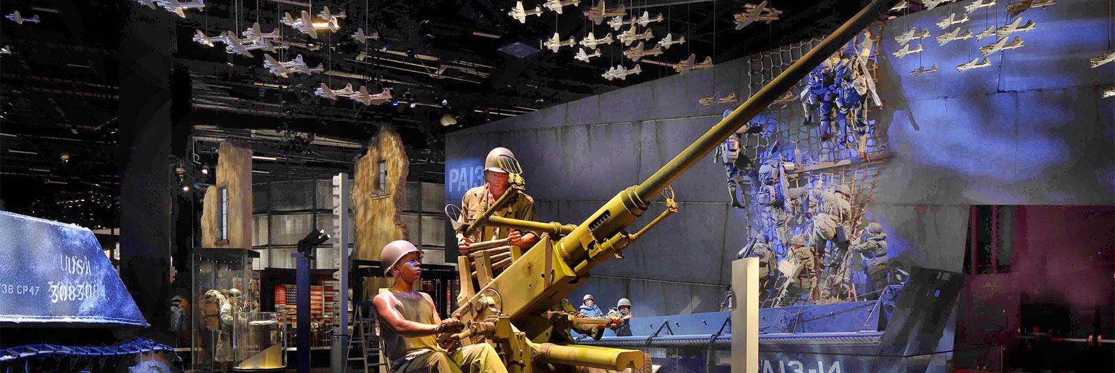 Exhibit space inside the National Museum of the United States Army featuring a tank and suspended planes on the ceiling.